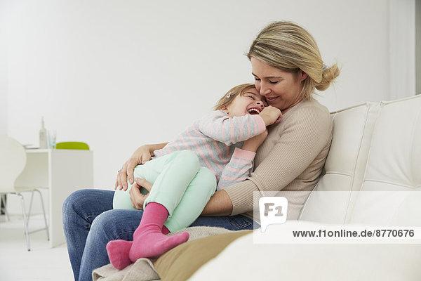Deutschland  München  Mutter und Tochter auf Sofa sitzend  kuschelnd