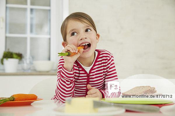 Mädchen am Tisch sitzend mit einem Haufen Karotten auf dem Kopf