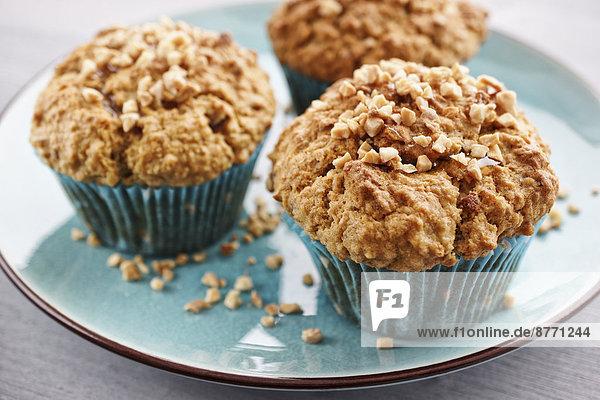 Teller mit drei Haferflocken-Muffins mit gebratenen und gehackten Mandeln