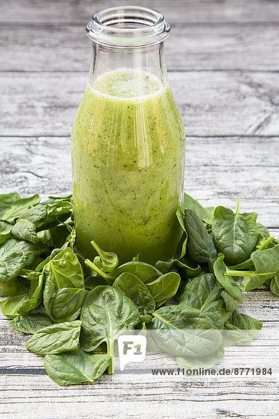 Glasflasche mit grünem Smoothie aus Spinat  Rucola  Apfel  Orange  Banane und Gurke inmitten von Babyspinatblättern auf grauem Holztisch