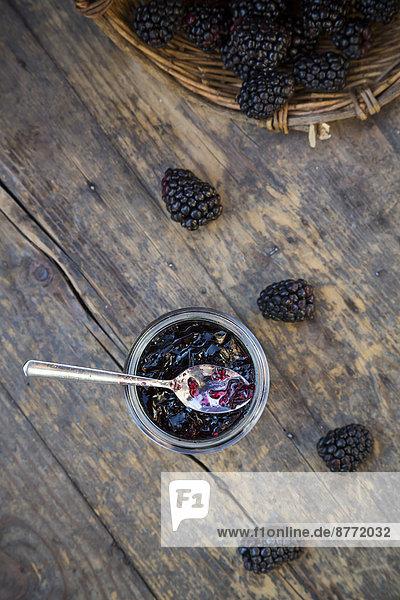 Basket of blackberries (Rubus sectio Rubus) and preserving jar of blackberriy jelly on wooden table