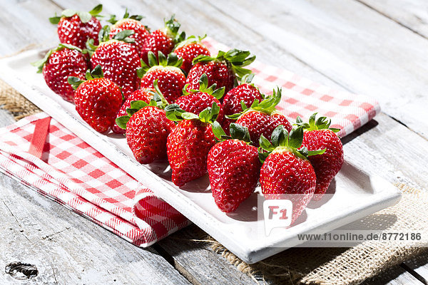 Platter of strawberries (Fragaria) on jute  kitchen towel and wooden table