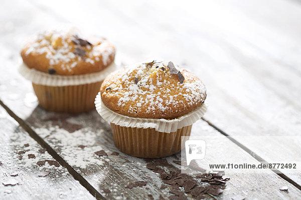Zwei Muffins in Pappbechern  bestreut mit Puderzucker und Schokoraspeln auf Holztisch