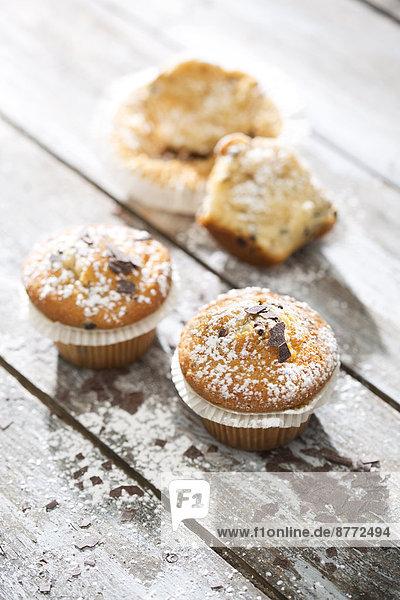 Zwei Muffins in Pappbechern und eine halbe im Hintergrund auf grauem Holztisch