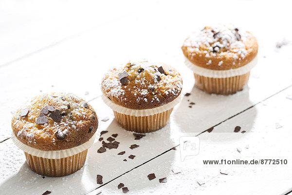 Drei Muffins in Pappbechern  bestreut mit Puderzucker und Schokoraspeln auf weißem Holztisch