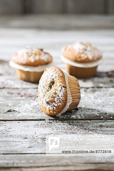 Drei Muffins in Pappbechern mit Puderzucker bestreut auf Holztisch