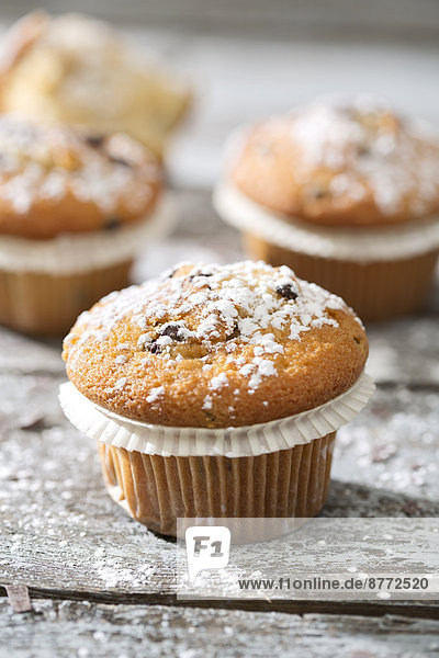 Muffins in paper cups sprinkled with powdered sugar on wooden table