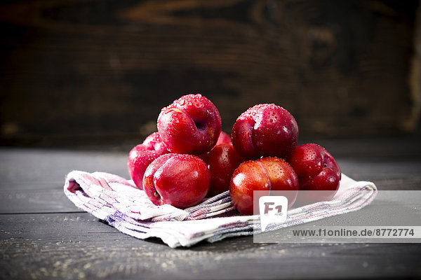 Pflaumenhaufen (Prunus salicina) auf Küchentuch und dunklem Holztisch