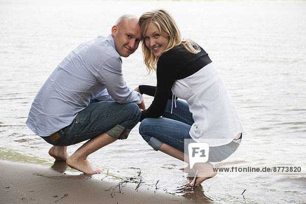Deutschland  Rheinland-Pfalz  junges Paar am Rheinufer hockend