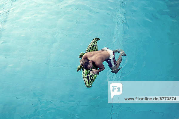 Young man with swim toy floating in water  view from above