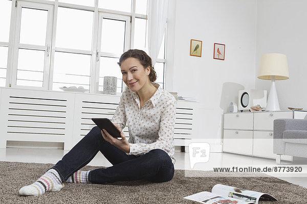 Frau zu Hause beim Lesen von E-Book