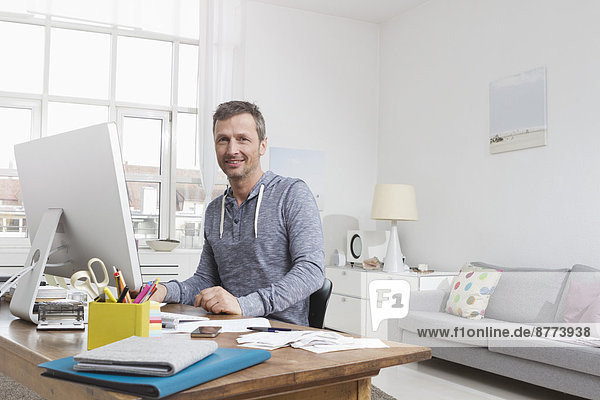 Man at home sitting at desk with computer