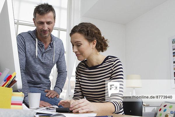 Mann und Frau zu Hause am Schreibtisch sitzend mit Rechnungen