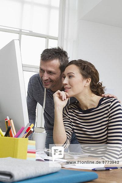 Mann und Frau zu Hause am Schreibtisch sitzend mit Computer