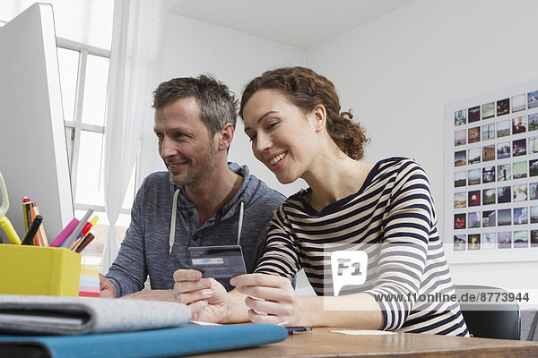 Couple at home sitting at desk shopping online