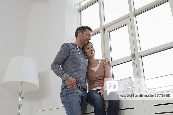 Smiling couple embracing at the window