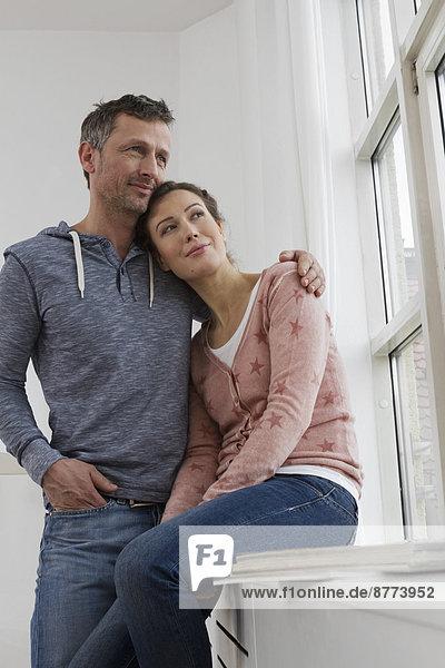 Lächelndes Paar umarmt am Fenster