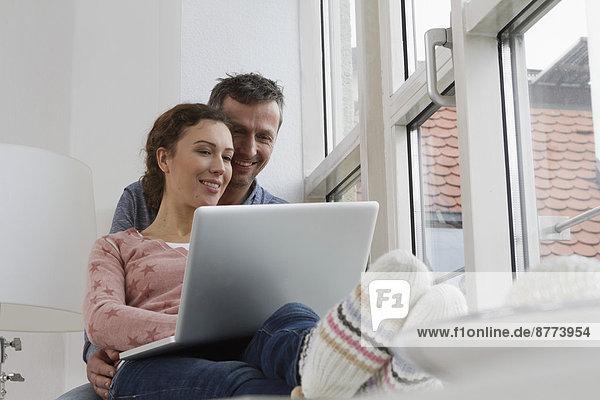 Paar sitzend auf der Fensterbank mit Laptop