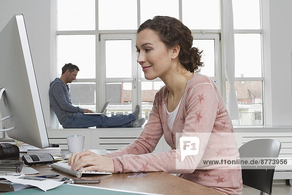 Smiling woman at desk with man in background