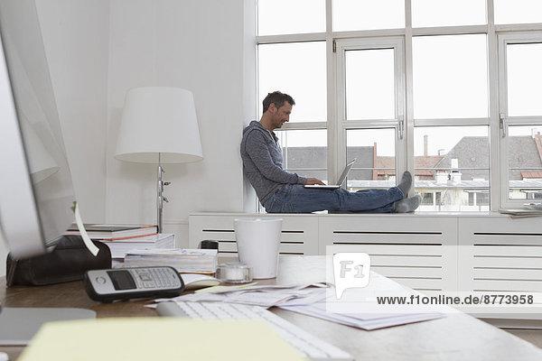 Man sitting on windowsill using laptop