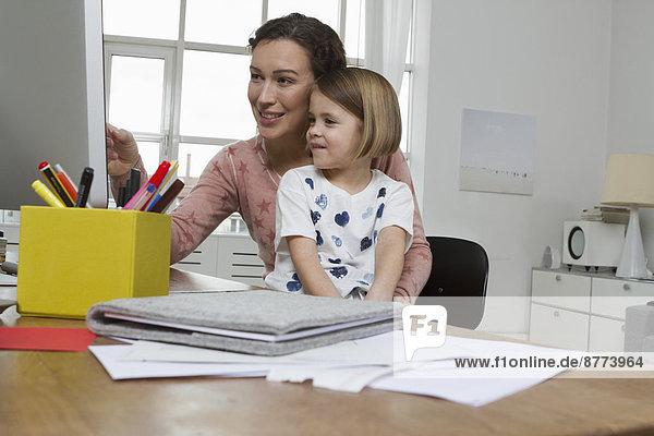 Mutter mit Tochter am Schreibtisch mit Blick auf den Computerbildschirm