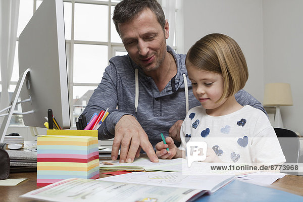 Vater mit Tochter am Schreibtisch zeichnen