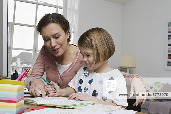 Mother with daughter at desk