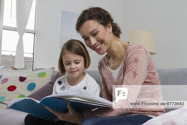 Mutter und Tochter auf Couch mit Buch