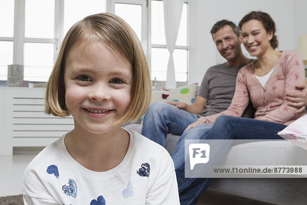 Blond girl in living room with parents in background