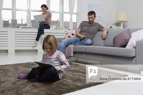 Mutter  Vater und Tochter mit tragbaren Geräten im Wohnzimmer