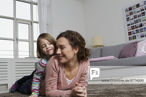 Happy mother and daughter lying on carpet in living room