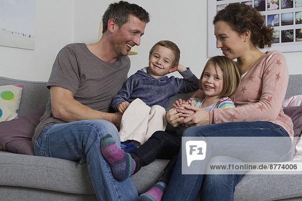 Glückliche vierköpfige Familie sitzt auf der Couch