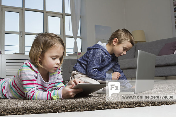 Bruder und Schwester mit Laptop und Tablet-Computer auf Teppich im Wohnzimmer