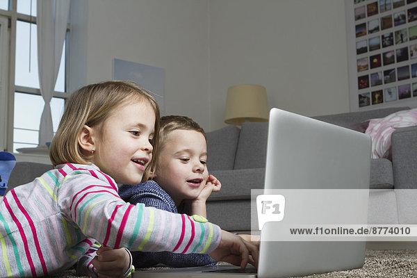 Bruder und Schwester mit Laptop auf Teppich im Wohnzimmer