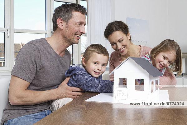Vierköpfige Familie mit Blick auf das Hausmodell