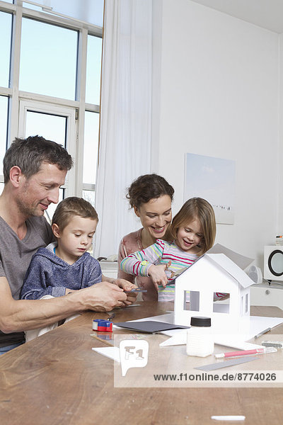 Family of four constructing house model
