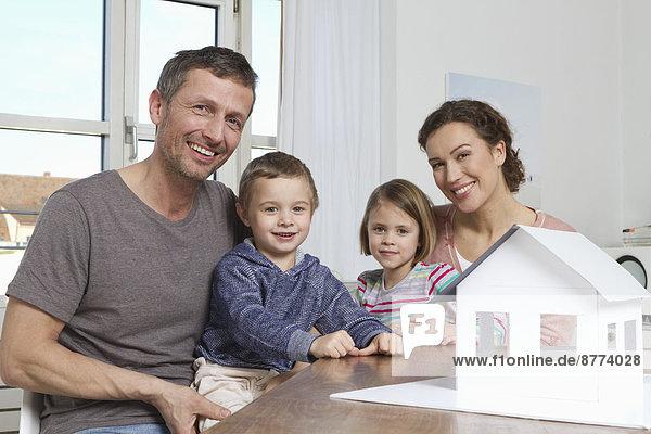 Vierköpfige Familie mit Hausmodell