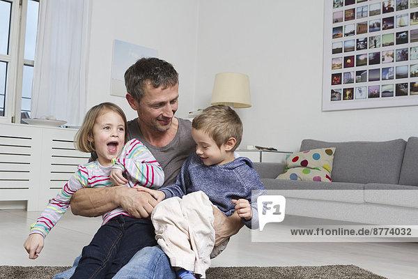Vater  Tochter und Sohn spielen im Wohnzimmer herum.