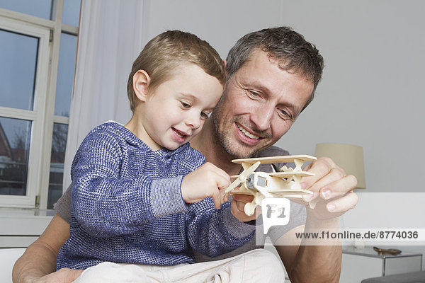 Father and son playing with model airplane