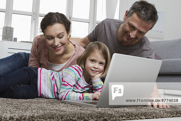 Vater  Mutter und Tochter mit Laptop auf Teppich im Wohnzimmer