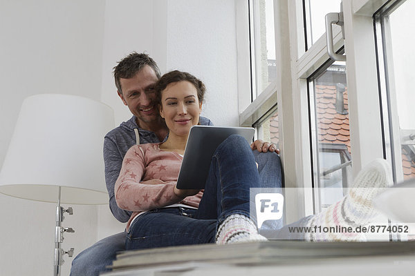 Couple sitting on windowsill using tablet computer