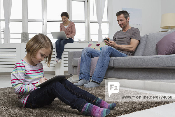 Mother  father and daughter using portable devices in living room