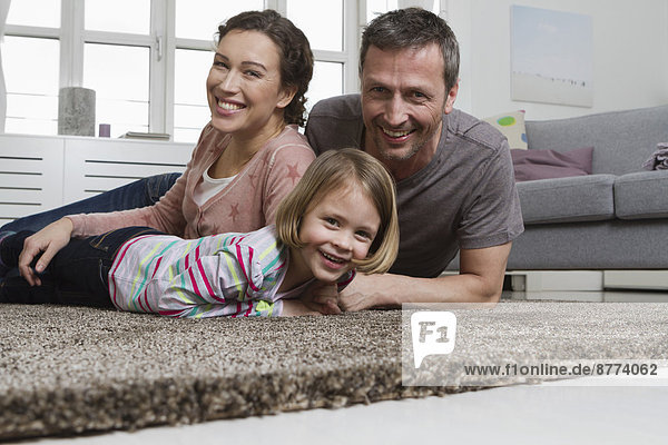 Happy mother  father and daughter lying on carpet in living room