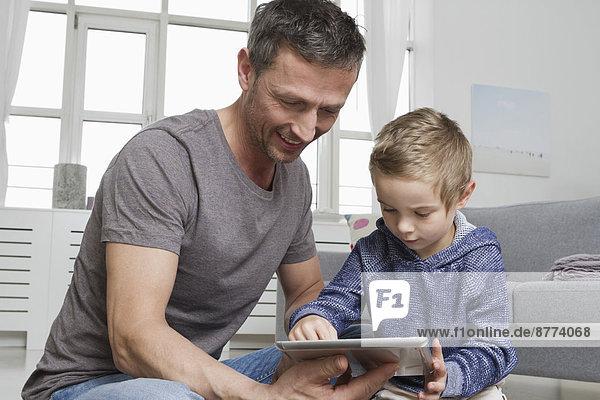 Vater und Sohn mit Tablet-Computer im Wohnzimmer
