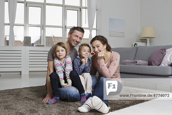 Happy family of four in living room
