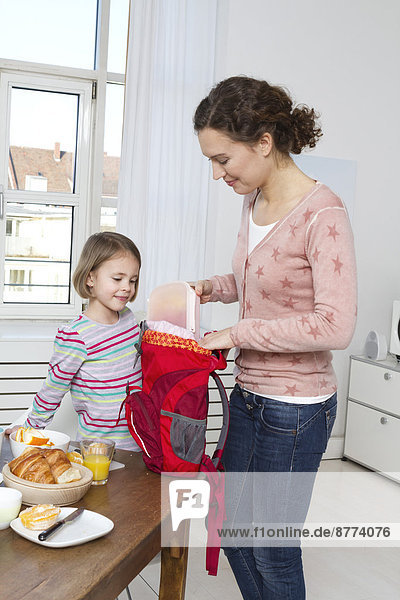 Mutter packt morgens den Rucksack ihrer Tochter.