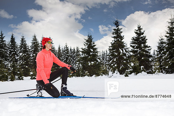 A woman cross-country skiing in the forest near Masserberg