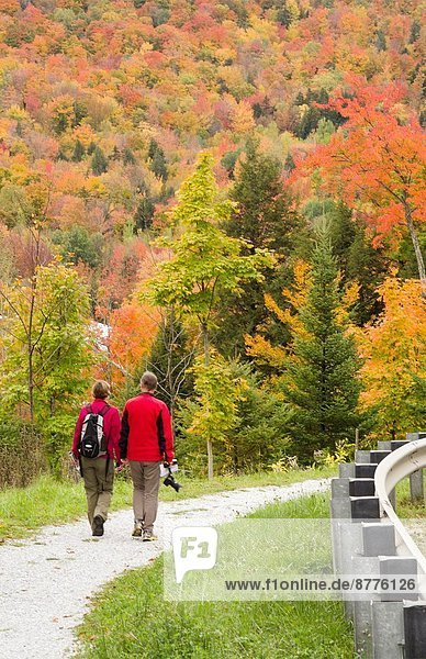 Littleton New Hampshire fall foliage colors tourist couple walking on trail in mountains 5.