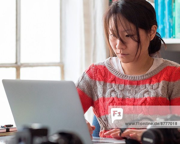 Young Asian woman in casual clothes works at the desk in her home office.