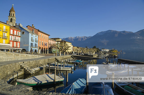 Alpine village ascona with blue sky and mountains and a small port with boats in ticino Switzerland  Europe